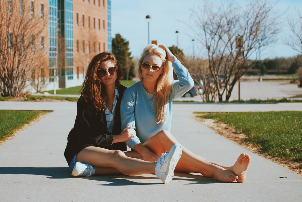 two women sitting close to each other on pathway