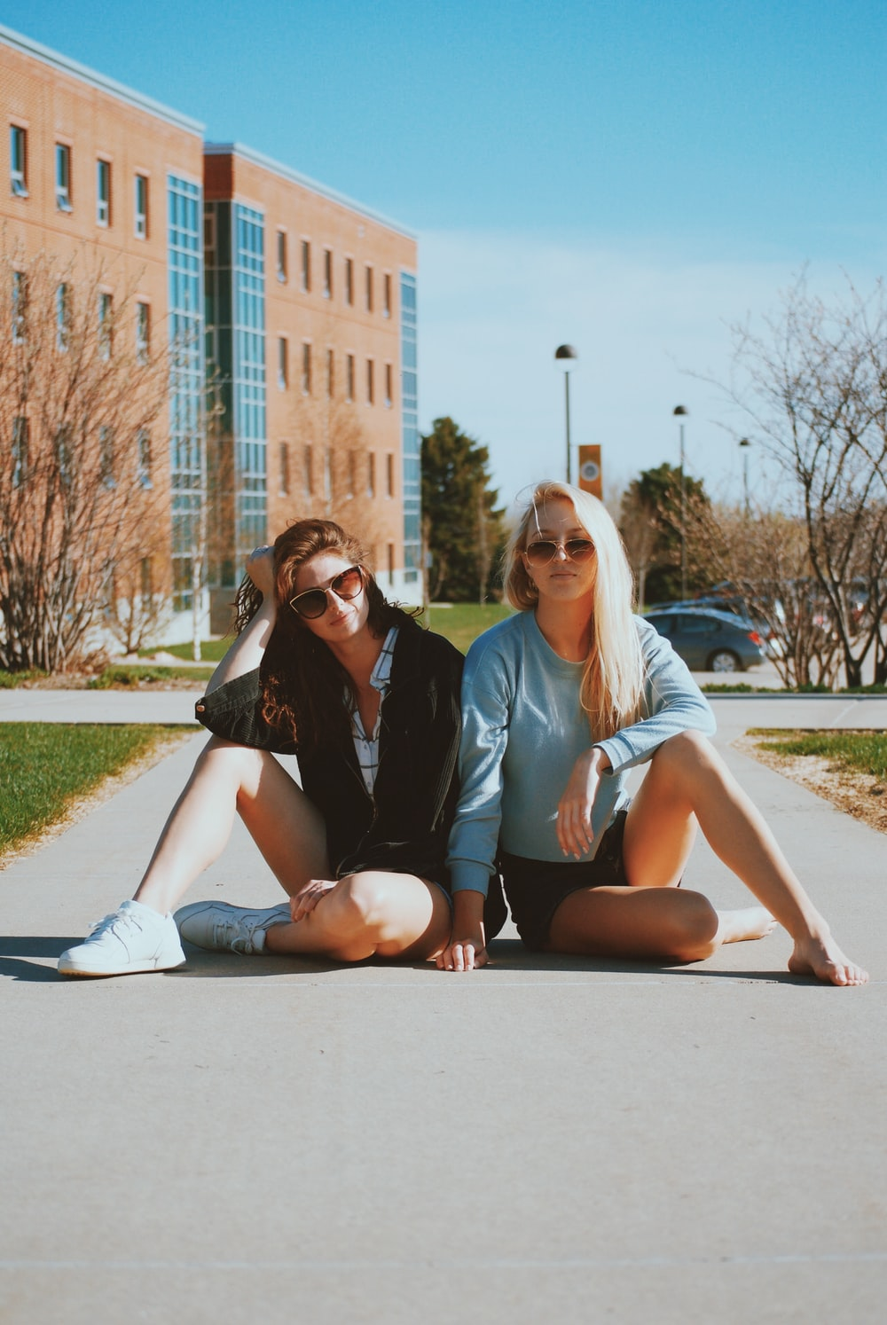 two women sitting on pathway beside each other