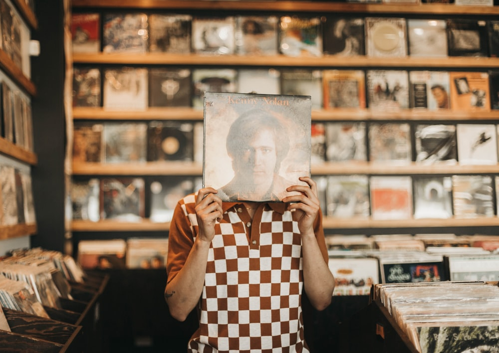 man in brown and white checked polo shirt holding up vinyl record sleeve over face