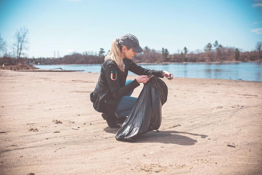 woman wearing jacket holding garbage bag