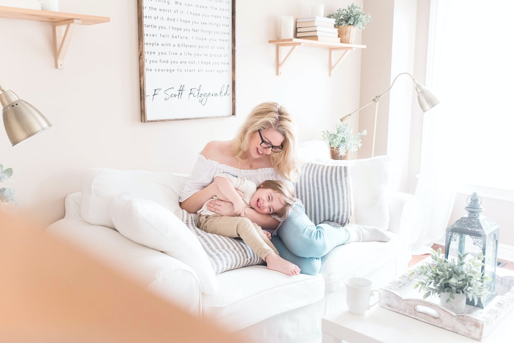 woman and baby sitting on white sofa