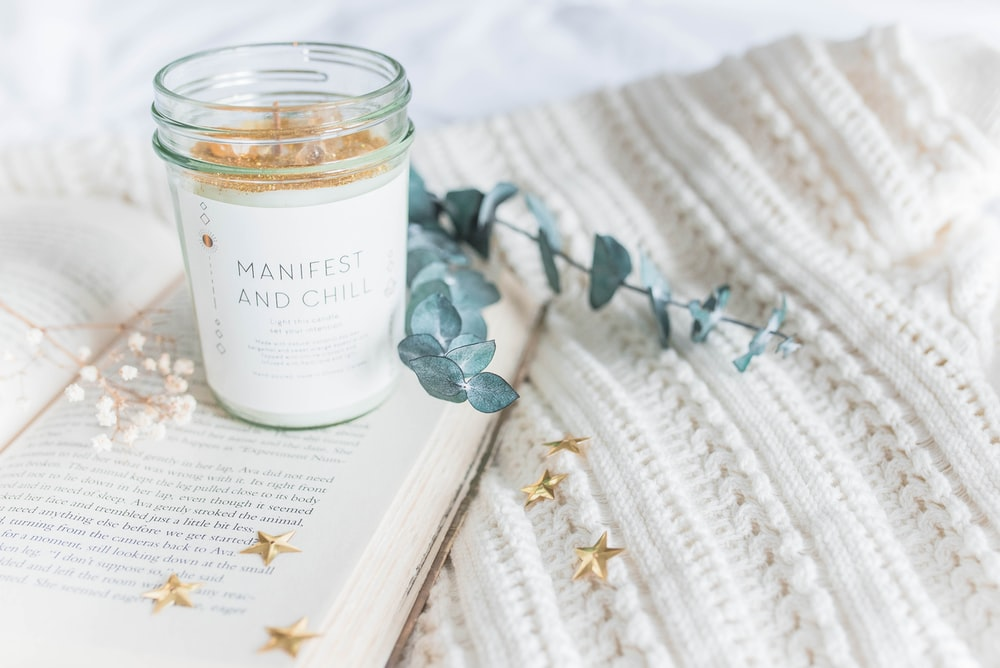 clear glass jar on opened book