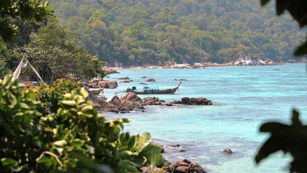 brown boat near rocks viewing sea