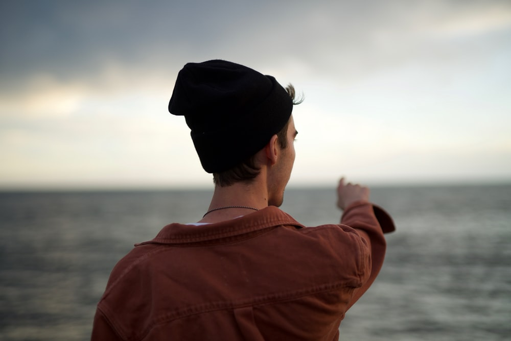 man wearing red jacket standing and pointing on sea
