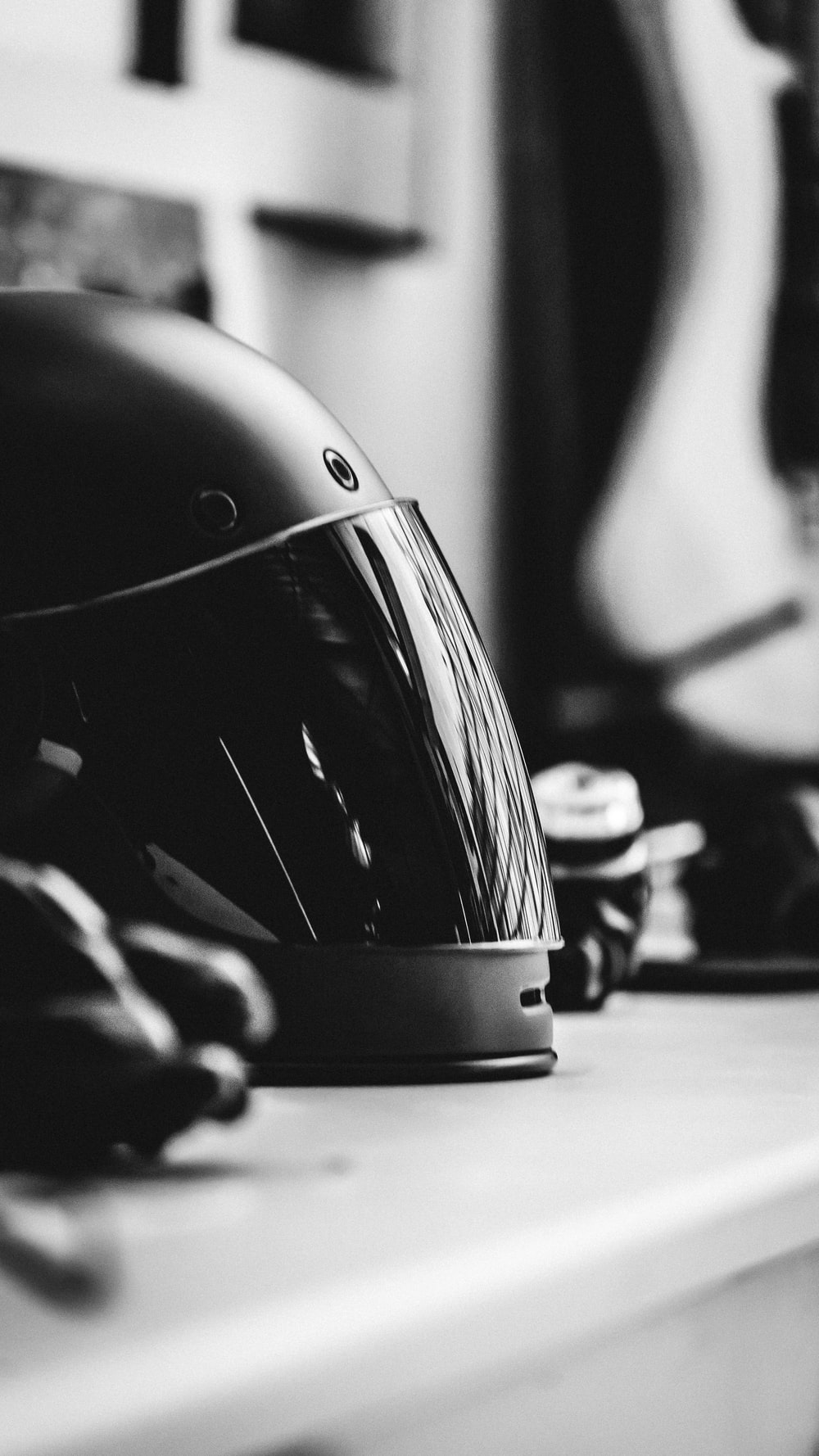 grayscale selective focus photography of full-face helmet on desk
