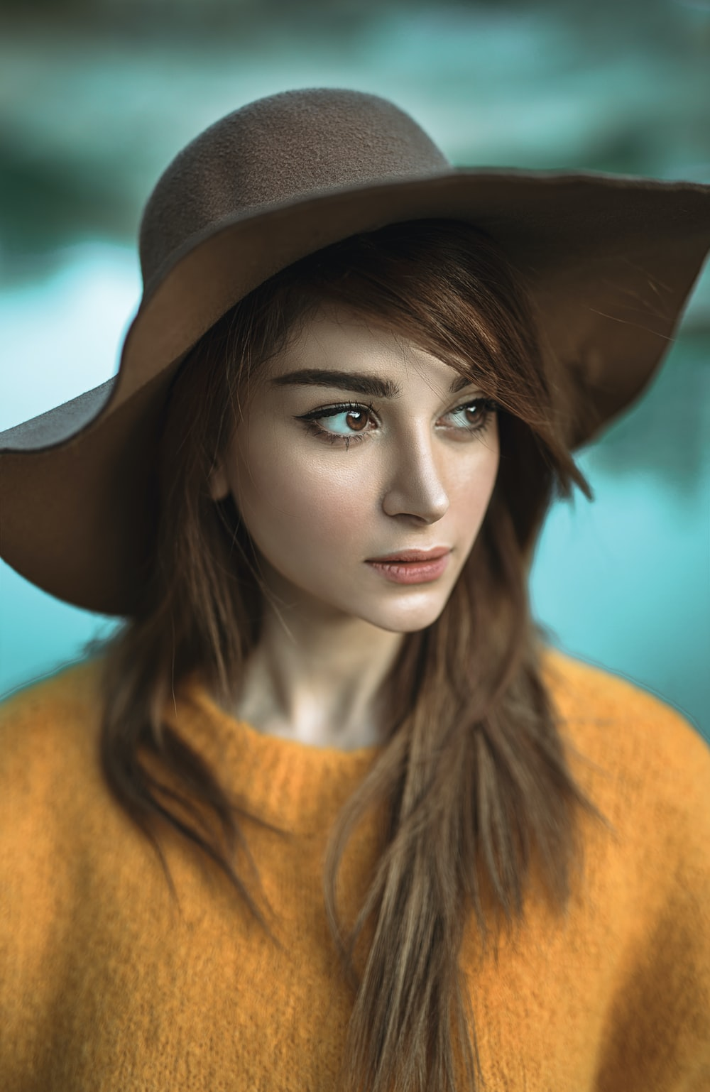 woman wearing yellow sweater and brown hat looking her right side