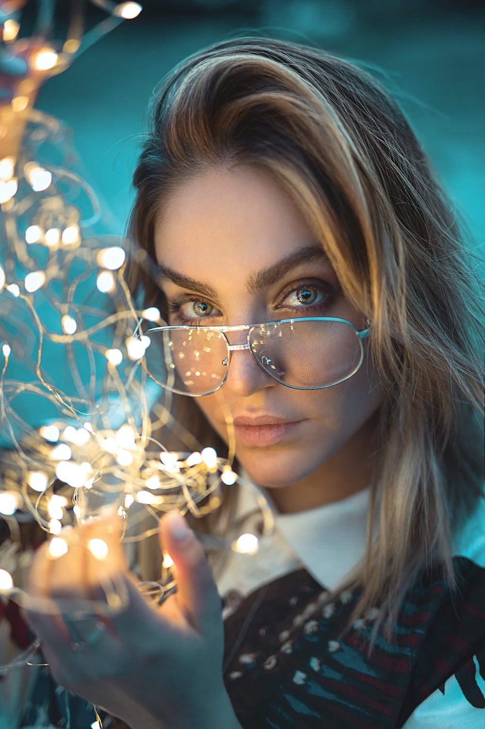 woman wearing eyeglasses holding white string lights