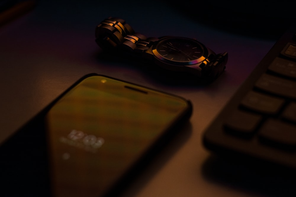 smartphone beside keyboard and watch