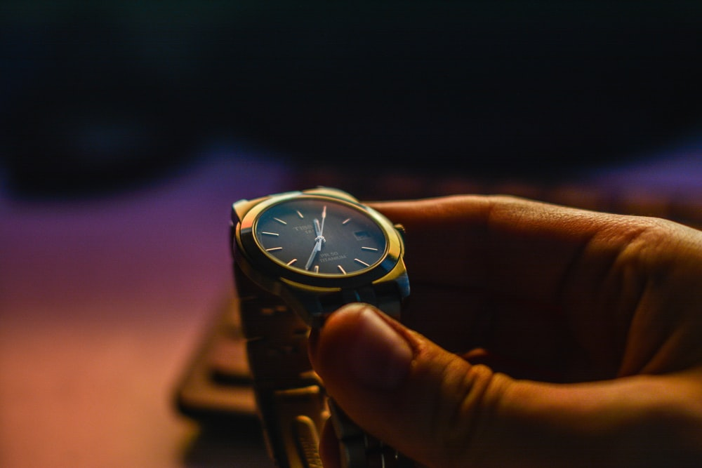 person holding silver-color analog watch