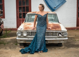 woman wearing blue off-shoulder dress standing in front of white classic vehicle