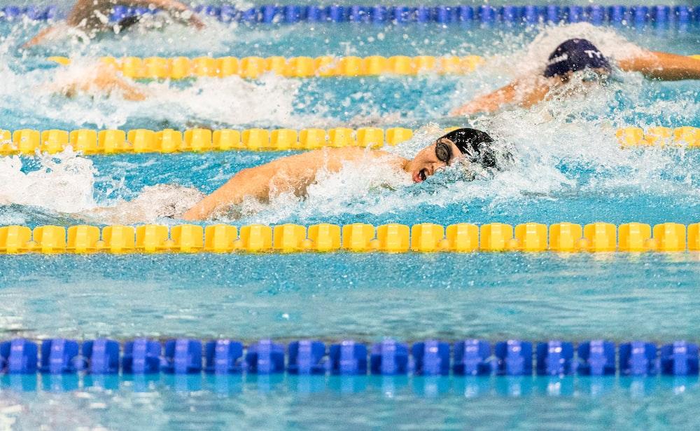 men swimming in pool