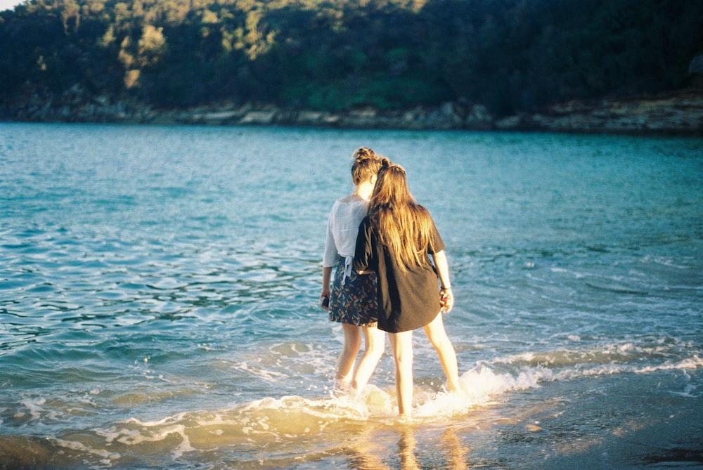 two women standing on seashore