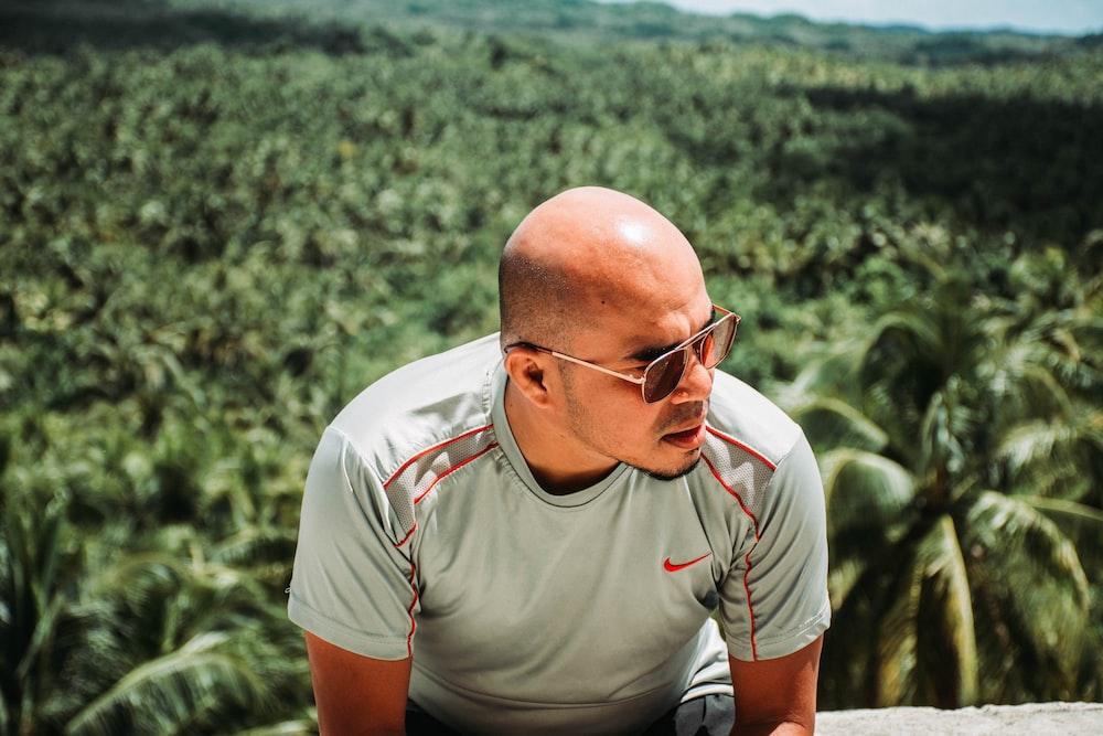 man wearing gray Nike crewneck shrt across green plants