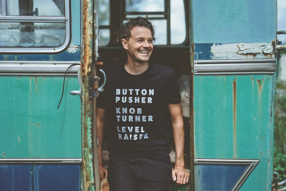 man in black crew-neck t-shirt standing beside bus