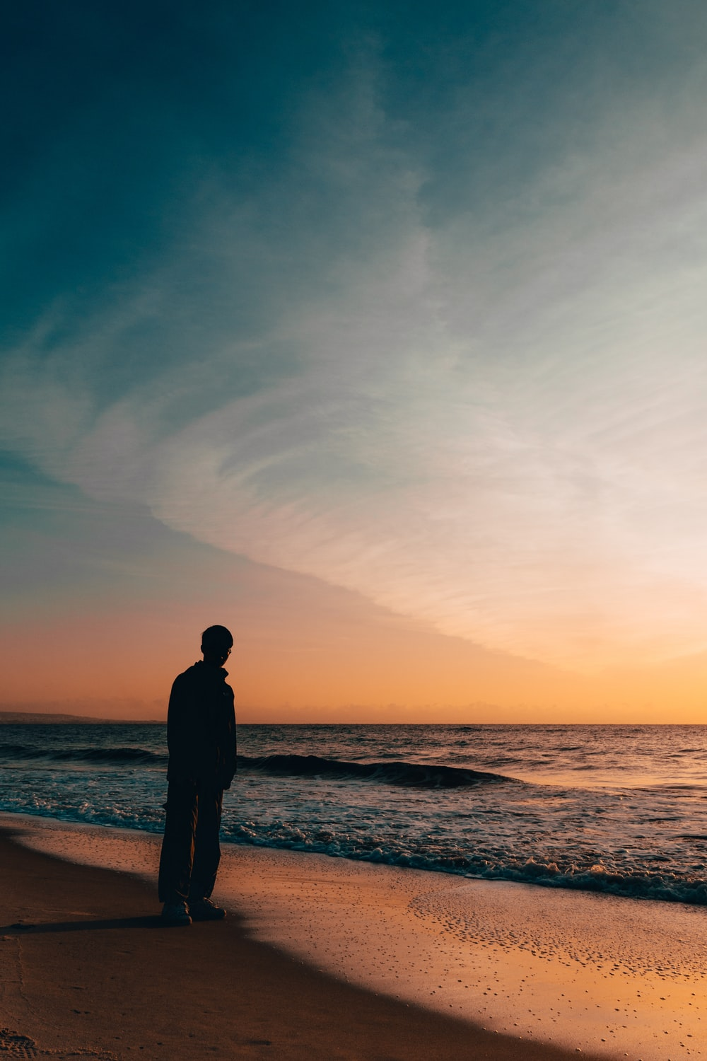 silhouette person standing beside seashore during sunset
