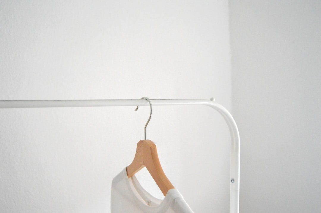 White shirt hanging on clothing rack in front of white wall