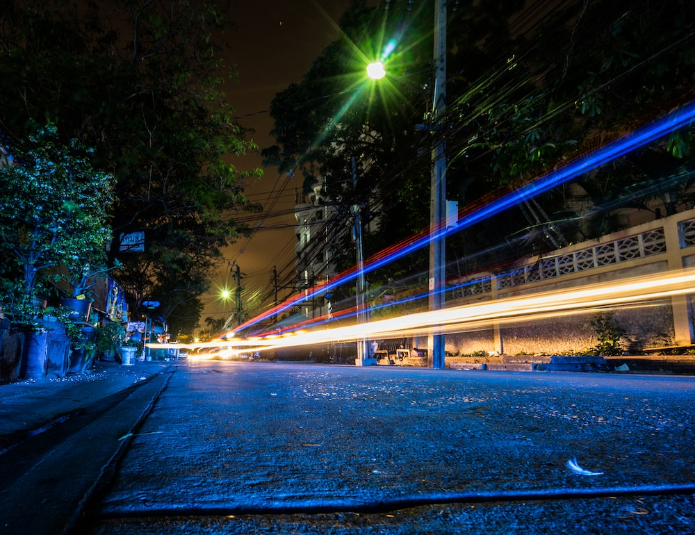 time lapse photography of vehicles passing by street during nighttime