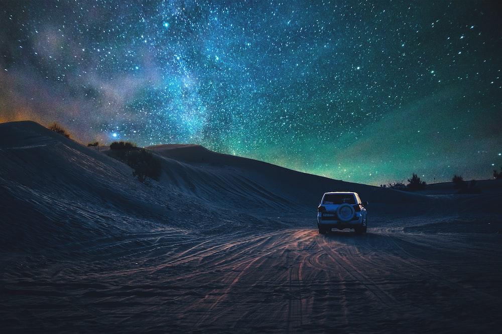 gray vehicle traveling on desert during nighttime