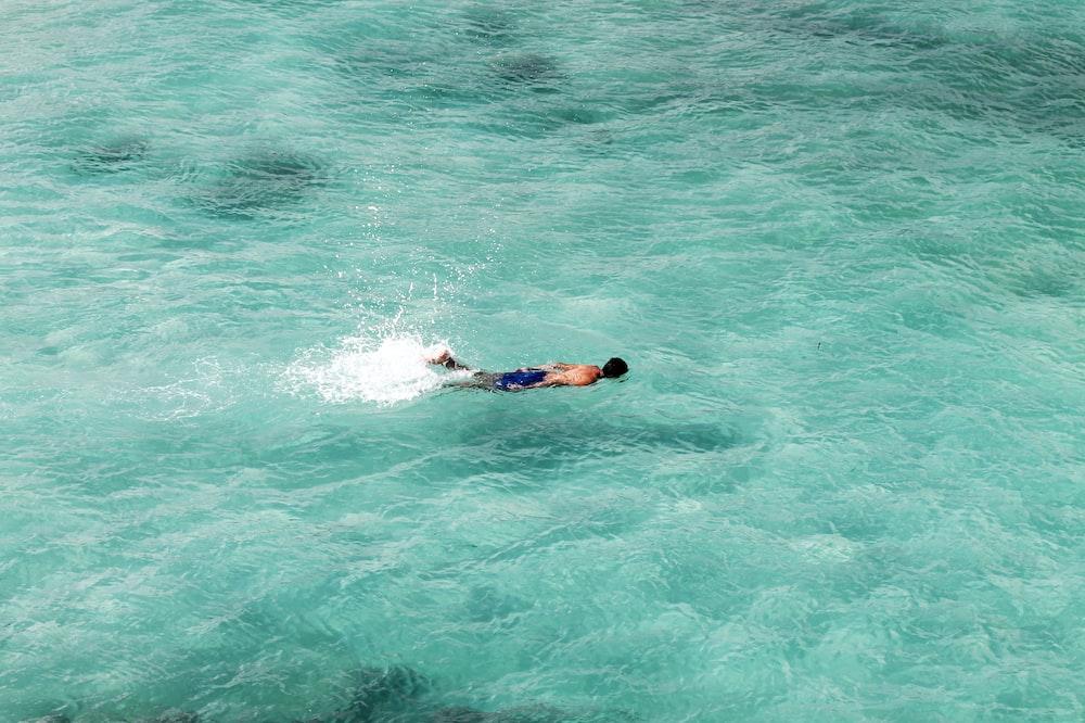 man swim on ocean