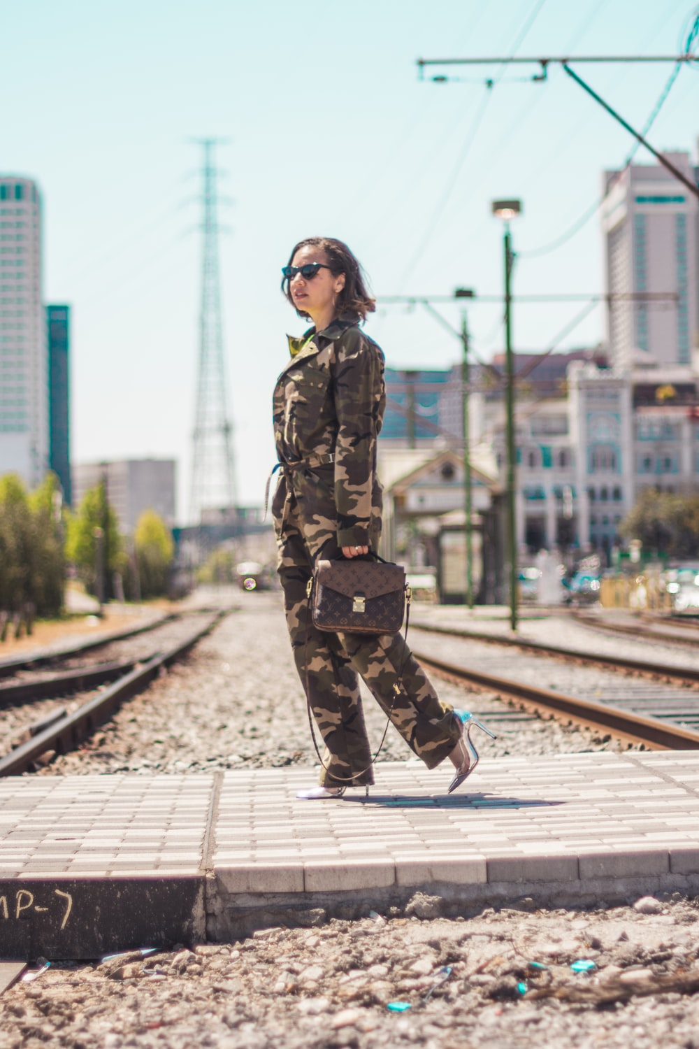woman wearing camouflage soldier uniform carrying brown 2-way leather bag
