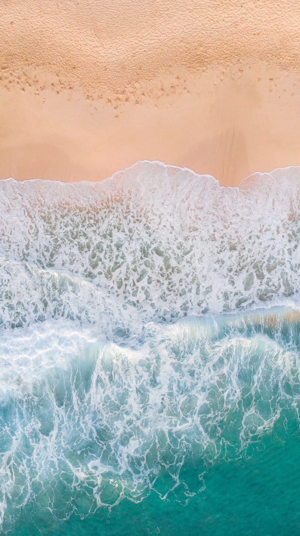 aerial photography of waves splashing on white sand beach