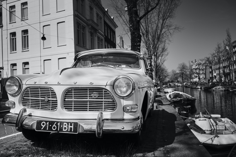 grayscale photography of vehicle beside building and tree\