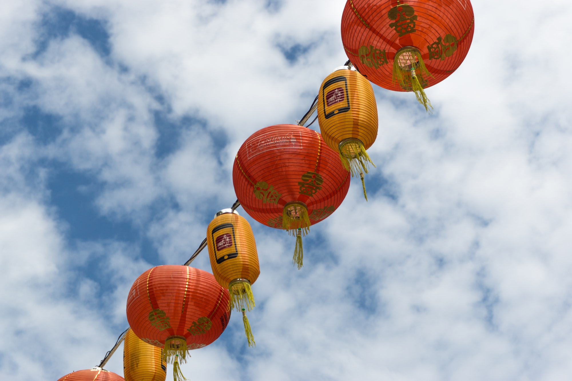 Chinese lanterns hanging high above with cloudy sky.
