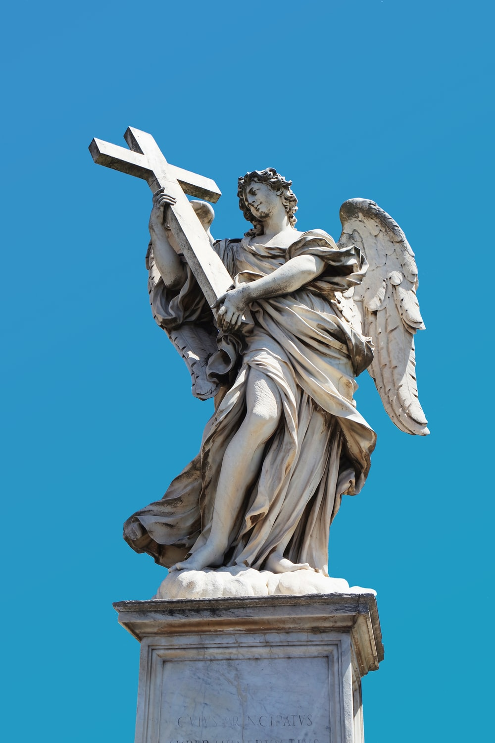 angel holding cross statue during day