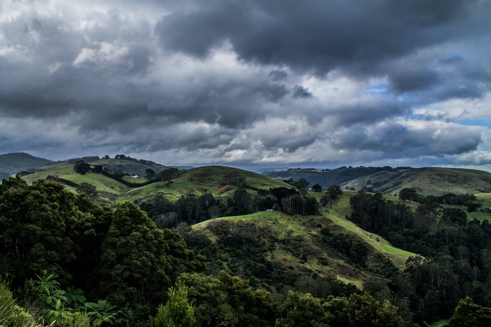 green field and mountain under gray and black skies
