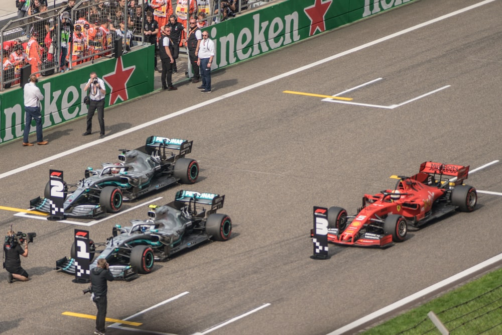 three F1 racing in road during daytime