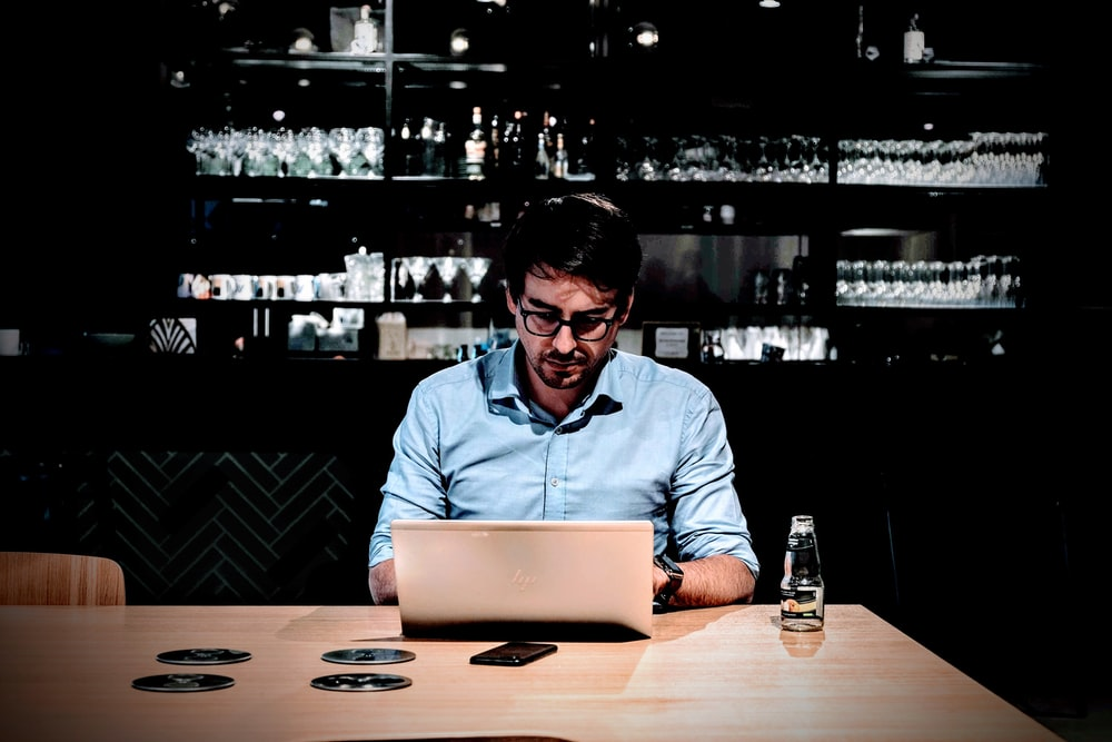 man wearing blue collared button-up long-sleeved shirt sitting and using laptop near table
