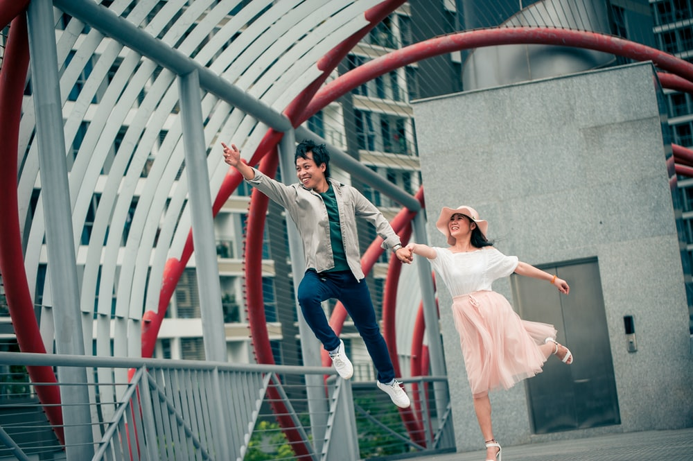 shallow focus photo of man and woman jumping