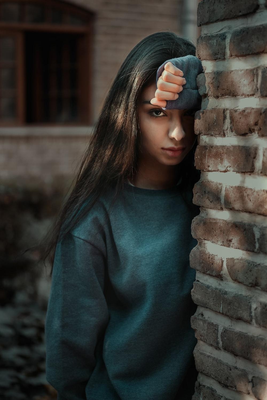woman in grey sweater standing behind brown brick wall