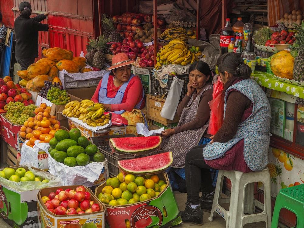 three women sitting behind assorted fruits on display in sidewalk