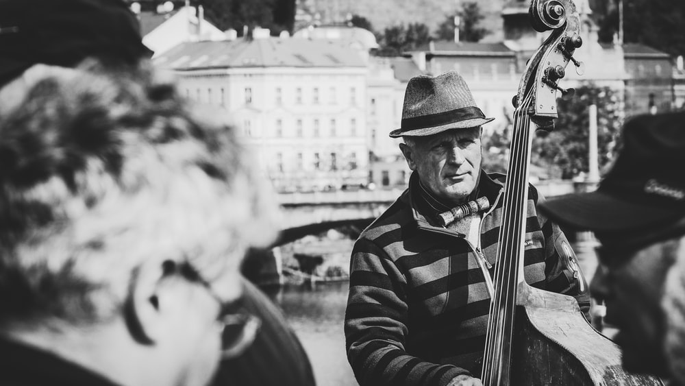 man playing cello selective focus photography