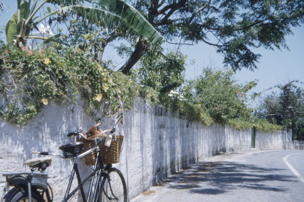 black bicycle parked beside wall