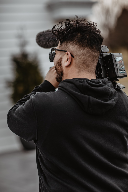close-up photo of man carrying recording camera