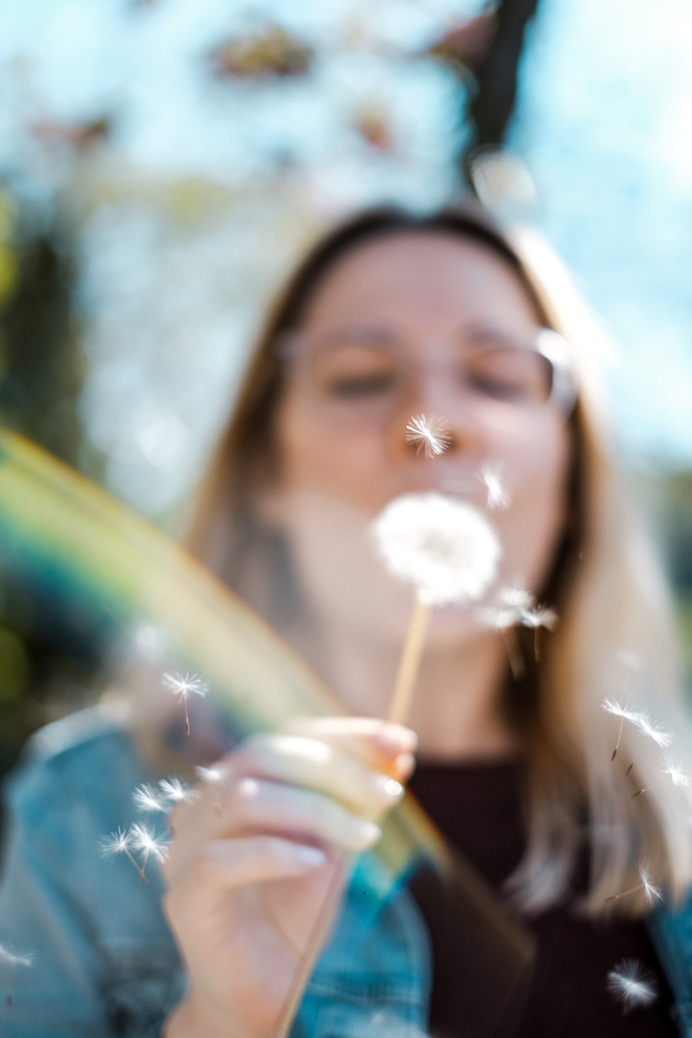 woman blowing white flower