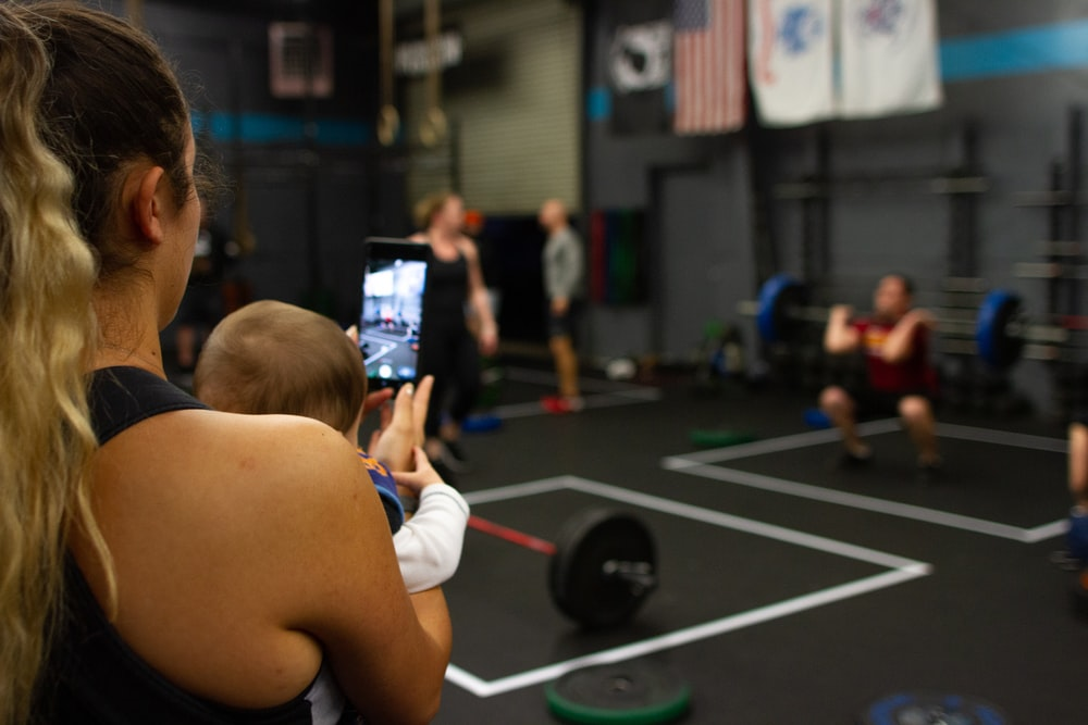 woman carrying baby while using smartphone inside gym
