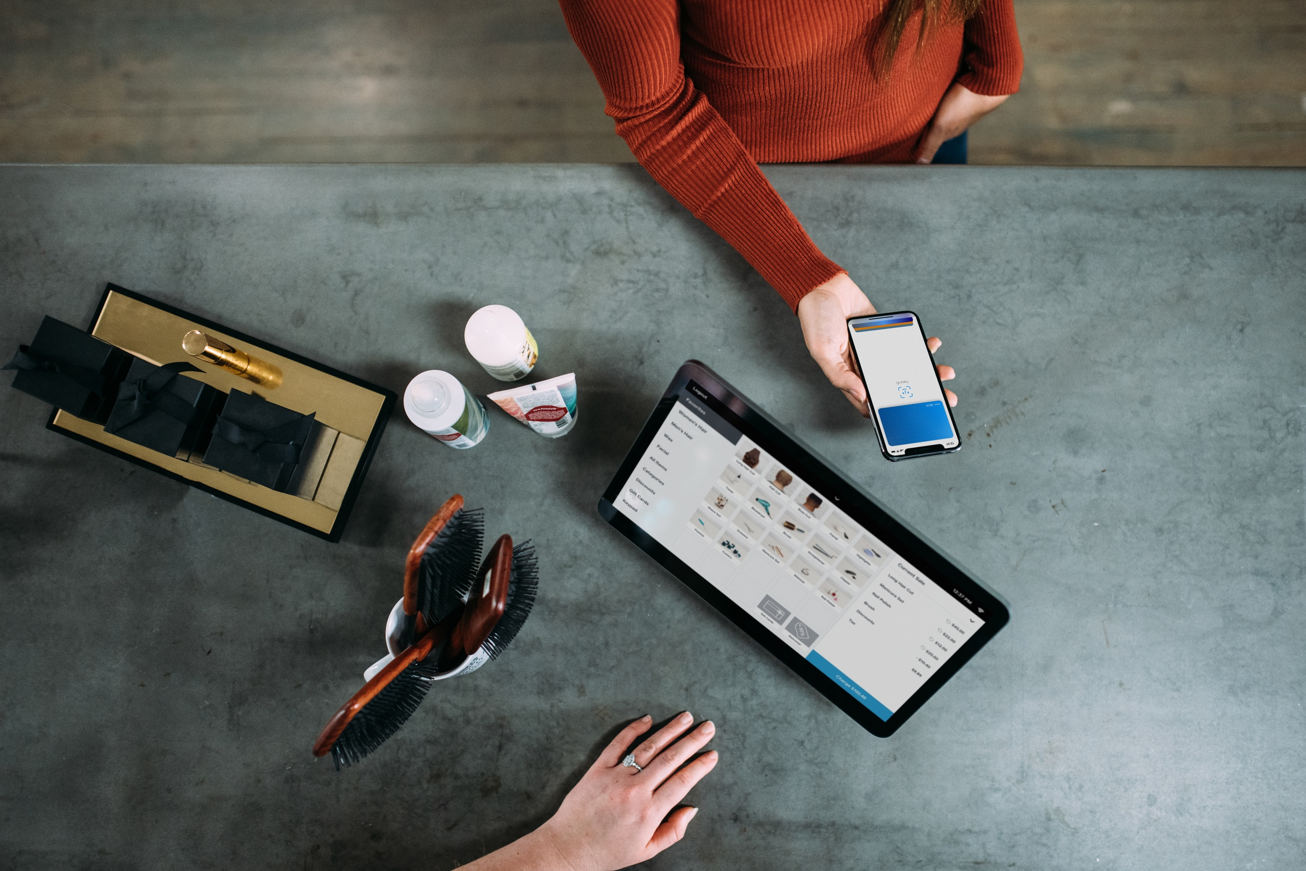 person holding smartphone beside tablet computer