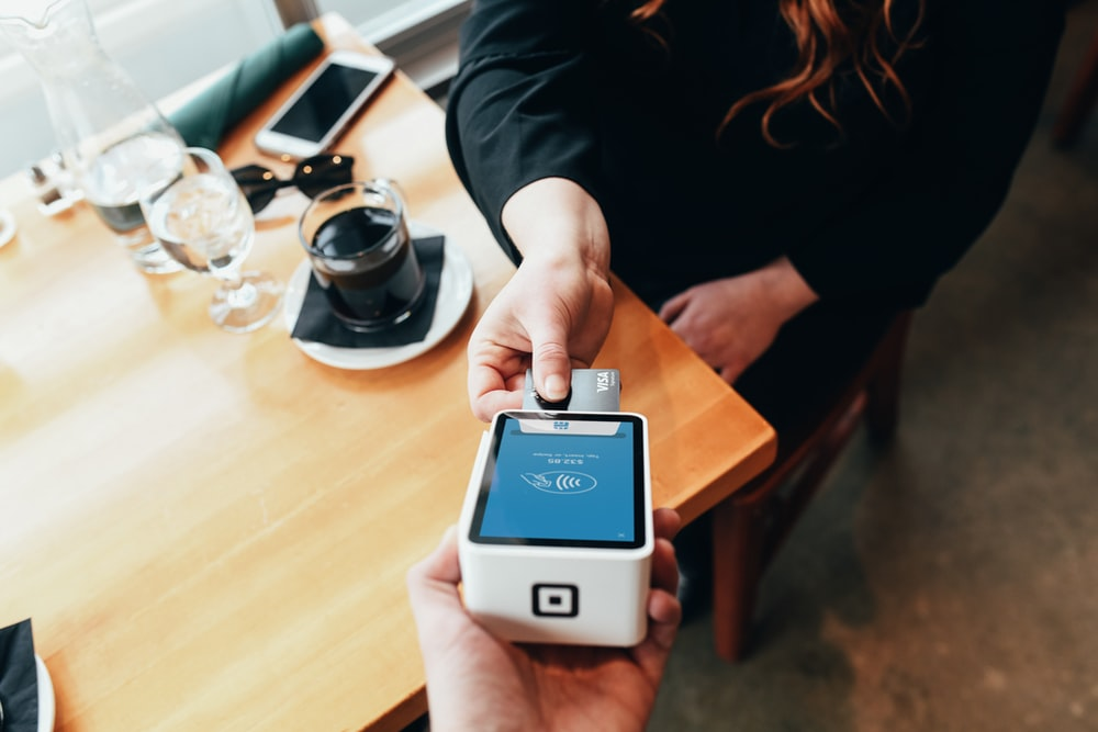 person holding credit card swipe machine
