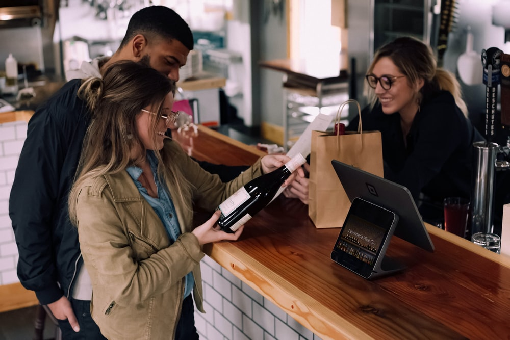 woman holding wine bottle beside man in front of woman smiling