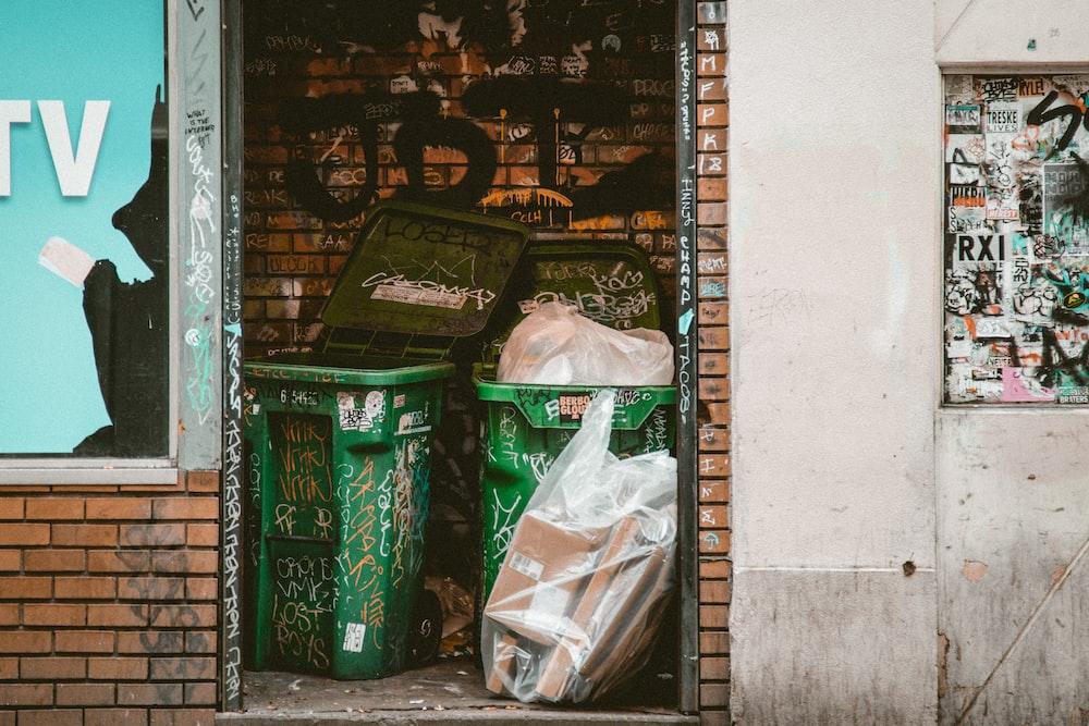 green dumpsters between brick walls