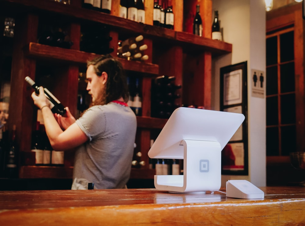 A staff at a wine store looking at the wine bottle intently to be familiar with it to help increase wine sales.