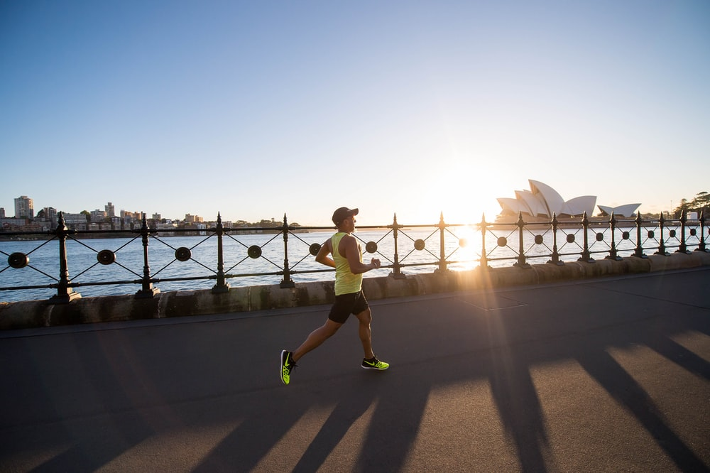 man running on bay walk during daytime