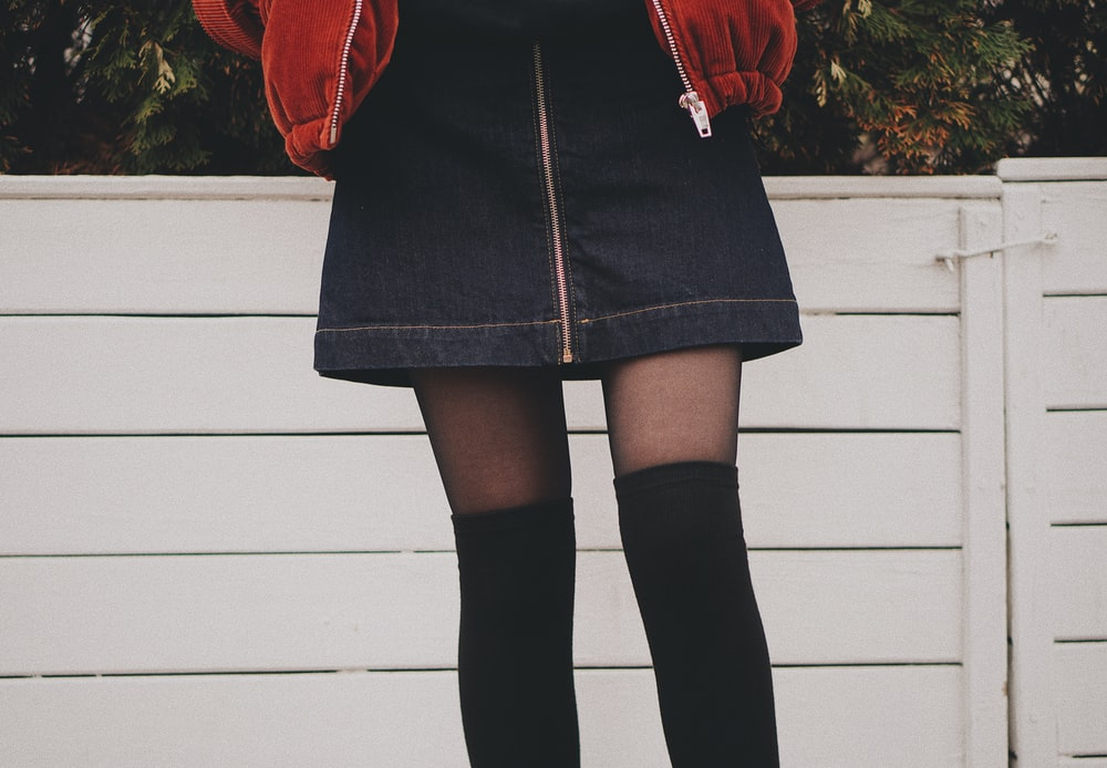 woman wearing black denim skirt and thigh high socks