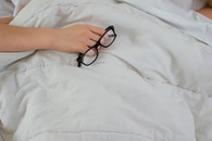 person lying on bed while covering face with pillow and holding eyeglasses
