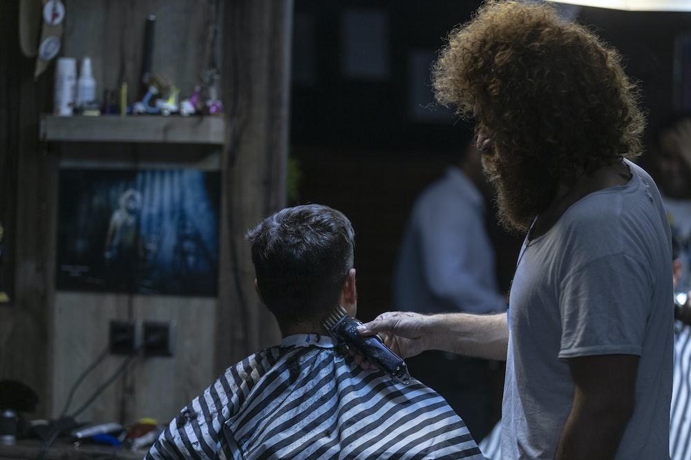 man cutting boy's hair on salon chair