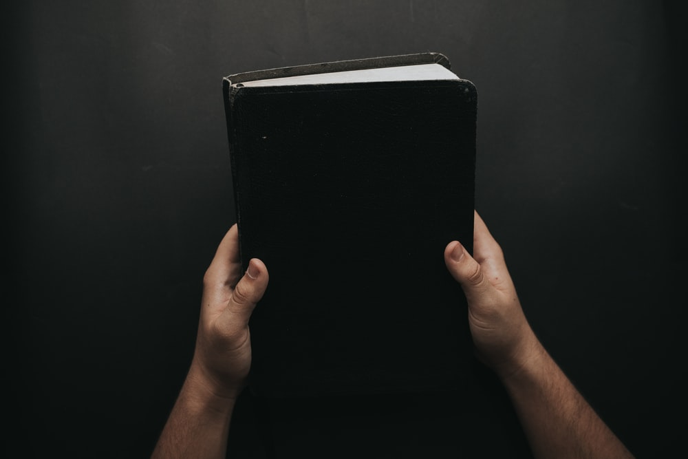person holding closed black book