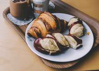 croissant on plate near ice cold drinks in cup beside gray stainless steel knife on brown tray